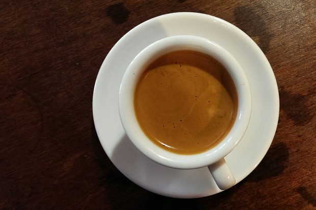 overhead view of a ceramic mug on a saucer full of frothy espresso