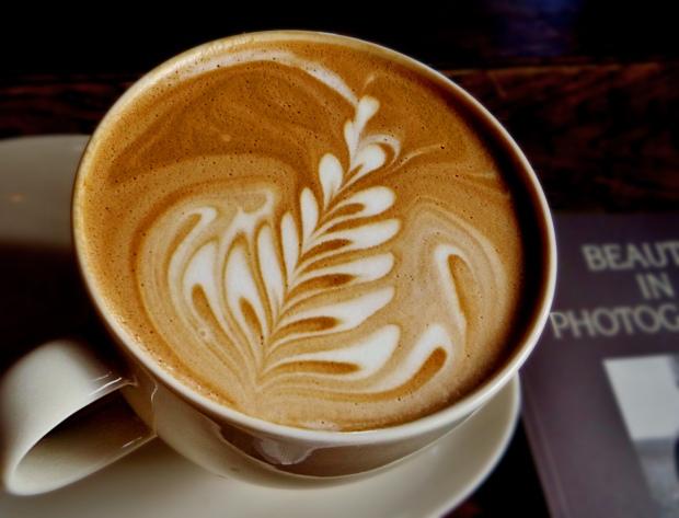 A cup of coffee with fancy latte art swirls in the foam